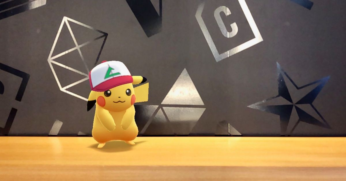 A Pikachu wearing Ash's hat is photobombing in Pokémon Go